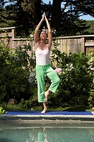 Mature woman meditating in a tree pose