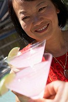 Close-up of a mature woman holding a martini