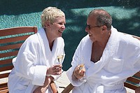 Close-up of a mature couple holding champagne flutes at poolside