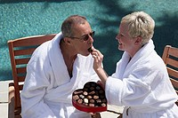 Close-up of a mature woman feeding a chocolate candy to a mature man