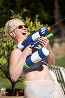 Close-up of a mature woman spraying water with a squirt gun