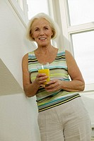 Senior woman holding glass of juice, smiling, portrait
