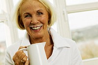 Senior woman holding milk jug, smiling, portrait, close-up
