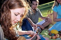 Young woman playing guitar for friends in garden, close-up