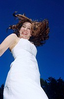 Young woman jumping, smiling, low angle view
