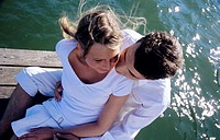 Young couple sitting on jetty, close-up