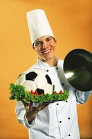 Chef serving football in plate