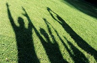 Human shadows on grass, raising arms