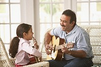 Hispanic father and daughter playing acoustic guitar, Richmond, Virginia, United States