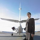 Businesswoman standing next to airplane, Perth, Australia