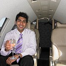 Young Indian businessman drinking inside airplane, Perth, Australia