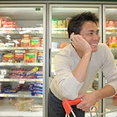 Asian man on cell phone at supermarket, Perth, Australia