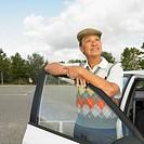 Senior Asian man leaning on car door, Perth, Australia