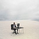 African businessman sitting at desk in the desert, Lancelin, Australia