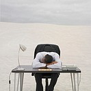 African businessman resting his head on help desk in the desert, Lancelin, Australia