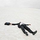 African businessman lying in the sand, Lancelin, Australia