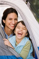 Hispanic mother and daughter laughing in tent