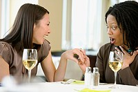 Woman showing friend engagement ring at restaurant