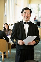 Asian male waiter at upscale restaurant