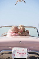 Senior couple kissing in pink convertible with Just Married sign, Las Vegas, Nevada, United States