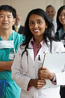 Female Indian doctor with co-workers in the background