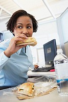 African American businesswoman eating lunch at desk