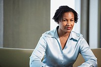 African American businesswoman sitting on sofa