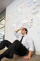 Tired businessman sitting on floor leaning against whiteboard wall
