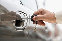 Close up of man's hand unlocking car door with key