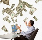 Studio shot of businessman at desk with money flying around him