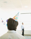 Rear view of man wearing party hat at office party