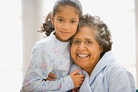 Hispanic grandmother and granddaughter in pajamas