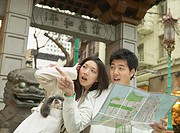 Young Asian couple looking at a map, San Francisco, California, United States