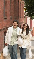 Young Asian couple walking down the sidewalk with shopping bags, San Francisco, California, United States