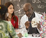African male science teacher showing students a human skull, Toronto, Canada
