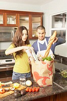 Young Hispanic couple unpacking grocery bag, San Rafael, California, United States