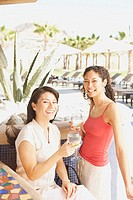 Two Hispanic women with drinks at hotel bar, Los Cabos, Mexico