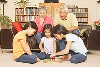Three young Asian sisters playing chinese checkers while grandparents watch, San Rafael, California, United States