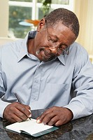 Senior African American man writing check