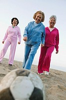 Group of senior women playing soccer at the beach