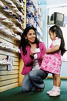 Hispanic mother and young daughter at shoe store, Port Washington, New York, United States