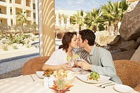 Couple kissing at the table in a resort hotel, Los Cabos, Mexico