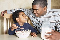 Young African American boy eating cereal with father