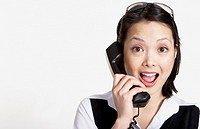 Studio shot of Asian businesswoman talking on telephone