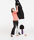 Studio shot of Asian businessman doing handstand with Asian businesswoman´s help