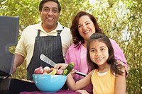 Hispanic family using barbecue grill