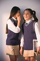 Two school girls in uniform whispering