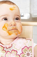 Baby girl (6-9 months) with food all over face, close-up