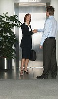 Businessman and woman shaking hands by elevator, woman smiling