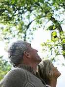 Mature couple standing under tree looking upwards, low angle view